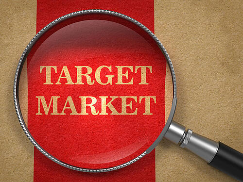 Target Market - Magnifying Glass on Old Paper with Red Vertical Line.